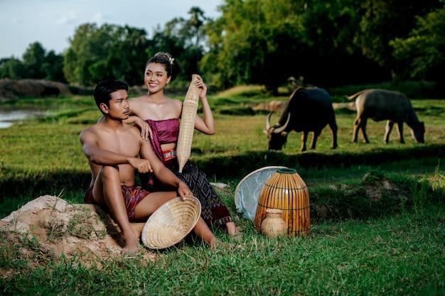 田舎のライフスタイルで美しい服を着てきれいな女性の近くに座っている肖像画の若い男トップレス
