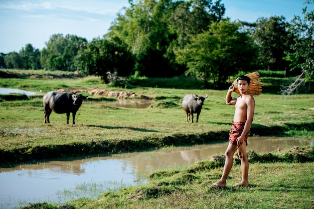 Portrait young man topless use bamboo fishing trap to catch fish for cooking