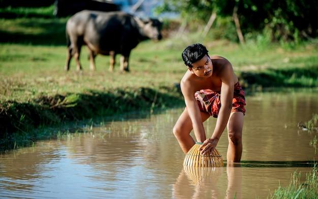 초상화 젊은 남자 토플리스는 요리를 위해 물고기를 잡기 위해 대나무 낚시 덫을 사용합니다