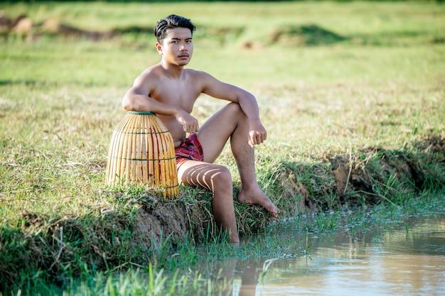 肖像画トップレスの若い男は、料理のために魚を捕まえるために竹の釣り罠を使用します
