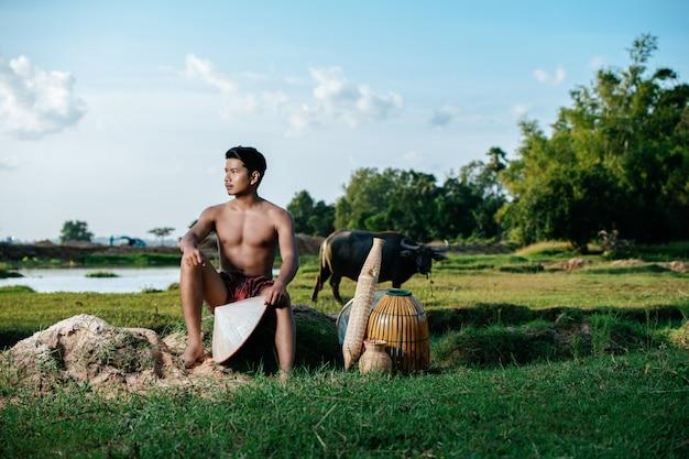 竹の釣り罠と一緒に座って田舎のライフスタイルでふんどしを着てトップレスの肖像画若い男