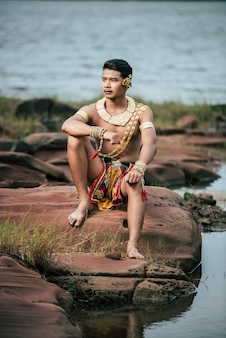 Portrait of young man in traditional costume posing in nature in thailand