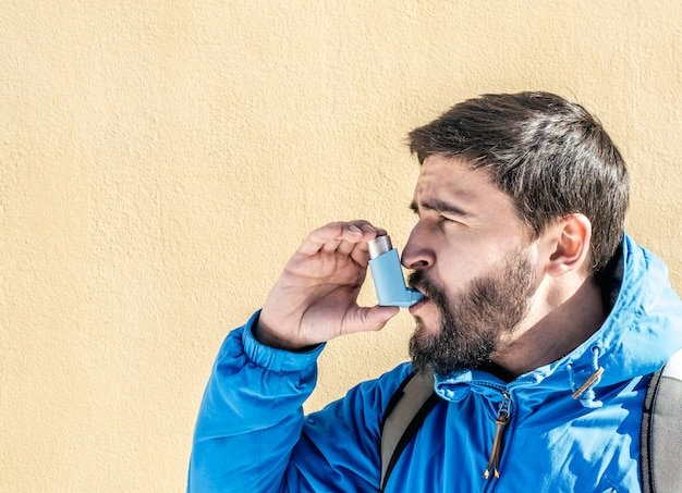 Portrait of young man using asthma inhaler outdoor