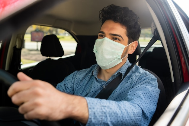 Portrait of young man using face mask while driving his car on his way to work. transport concept. new normal lifestyle concept.