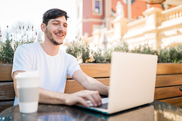Portrait of young man using his laptop while sitting in a coffee shop. technology and lifestyle concept.