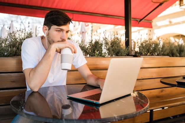 Ritratto di giovane uomo utilizzando il suo computer portatile mentre è seduto in una caffetteria. concetto di tecnologia e stile di vita.