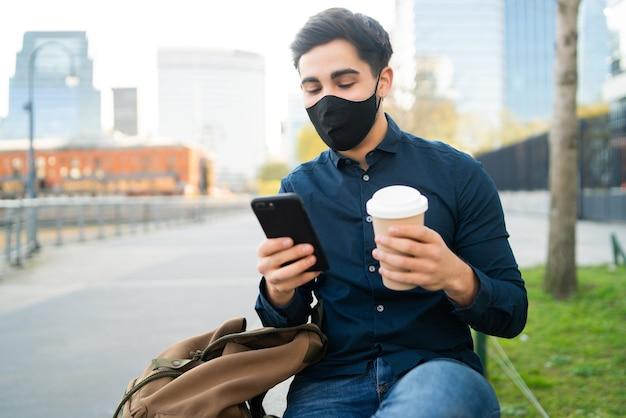 Ritratto di giovane uomo utilizzando il suo telefono cellulare e tenendo una tazza di caffè mentre è seduto su una panchina all'aperto