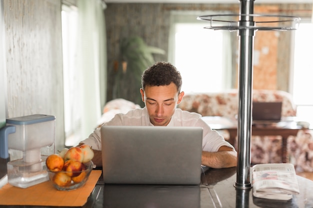 Portrait of young man using laptop at home