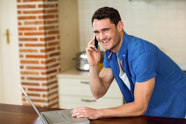 Portrait of young man using laptop and talking on phone in kitchen