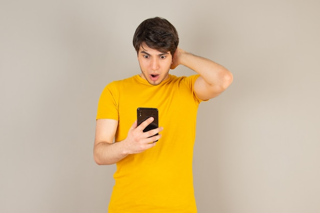 Portrait of a young man using a mobile phone against gray.