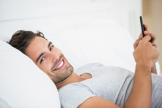 Portrait of young man using mobile phone on bed
