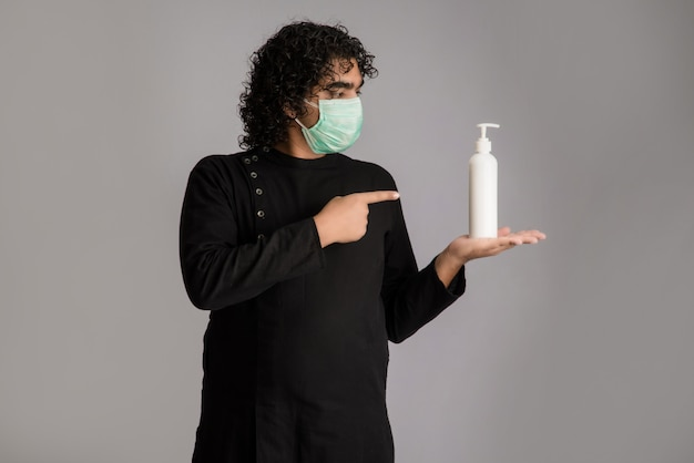 Portrait of young man using or showing a sanitizing gel from a bottle for hands cleaning.