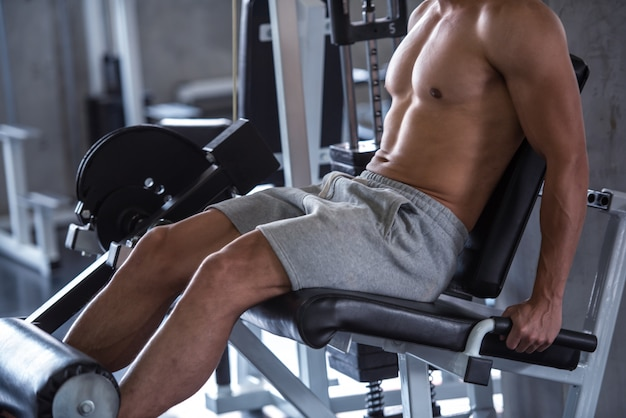 Portrait of young man using weight lifting equipment for legs, bodybuilder concept, close up.
