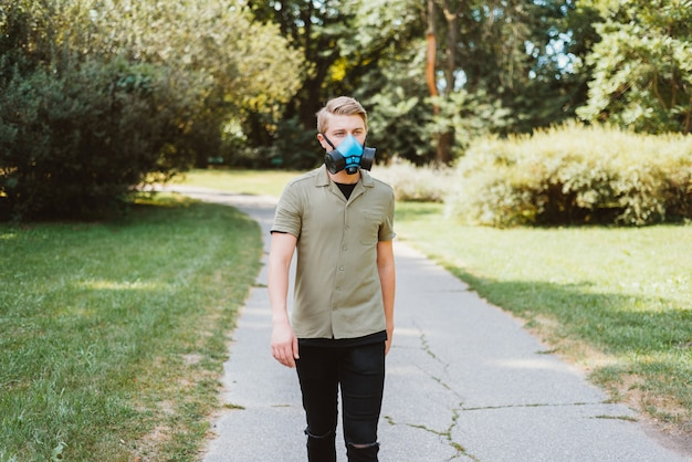 Portrait of young man walking in park and wearing respirator, be safe covid19.