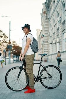 Ritratto del giovane che cammina con la bicicletta meditatamente classica