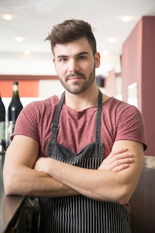 Portrait of young man wearing apron standing in the bar