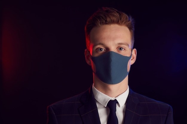 Portrait of young man wearing face mask and looking at camera while posing at party standing against black background, copy space