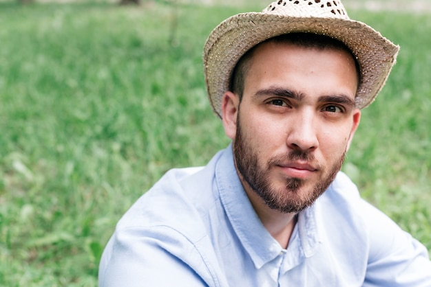 Portrait of young man wearing hat looking at camera sitting on grass