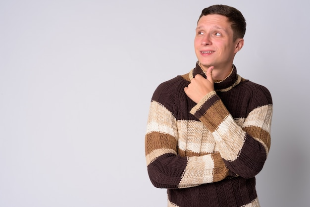 Portrait of young man wearing turtleneck sweater ready for winter against white wall