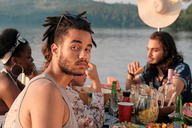 Portrait of young man  while having dinner at the table together with his friends outdoors