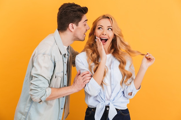 Portrait of young man whispering secret or interesting gossip to happy beautiful woman in her ear, isolated over yellow wall