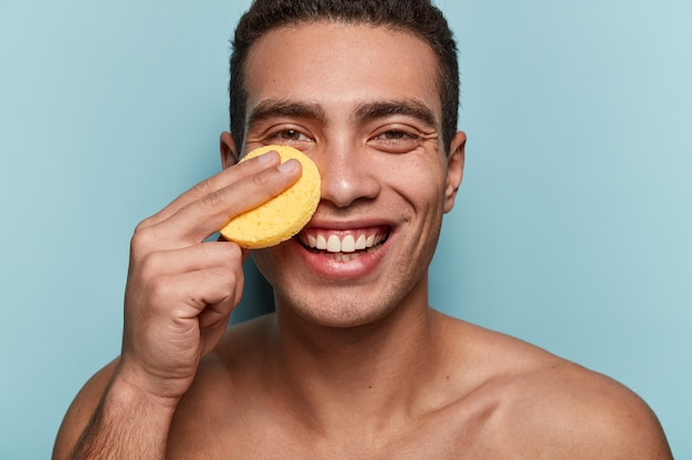 Portrait of young man wiping face with sponge