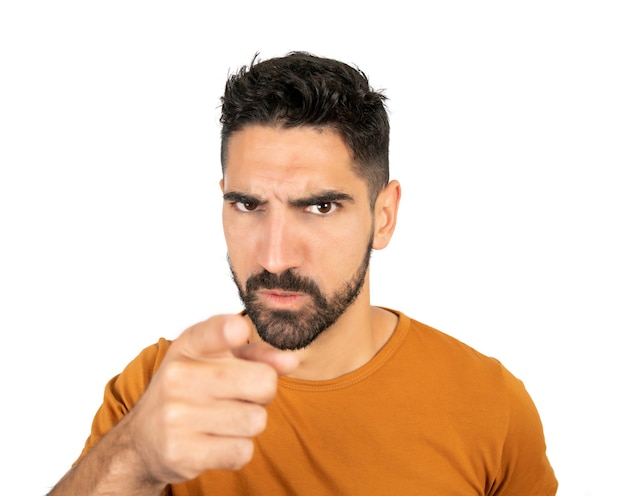 Portrait of young man with angry expression and pointing someone against white wall
