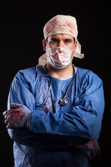 Portrait of young man with arms crossed dressed up like a crazy doctor covered with blood for halloween. bizzare medical practitioner.