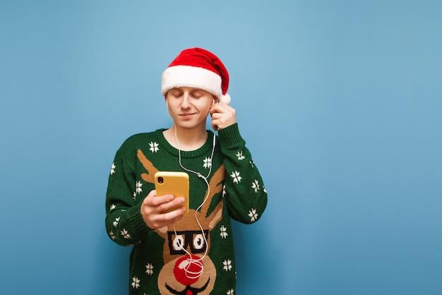音楽を聴くクリスマスの肖像画の若い男