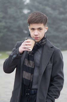 Portrait of a young man with cup of coffee, foggy winter weather. photo in gray tones