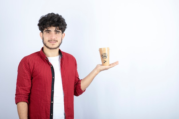 Portrait of young man with cup of coffee standing on white background. high quality photo