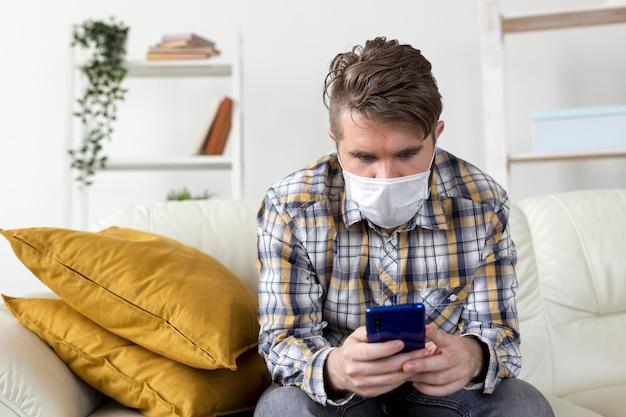 Ritratto di giovane uomo con maschera per il viso navigando sul telefono cellulare