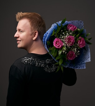 Portrait of a young man with flowers bouquet on dark