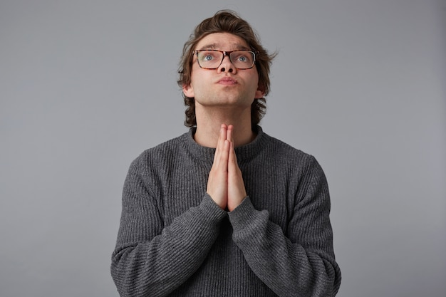 Portrait of young man with glasses wears in gray sweater, stands over gray background and looks up, has sorrorful expression, keeps palms in praying gesture, believes in something good.
