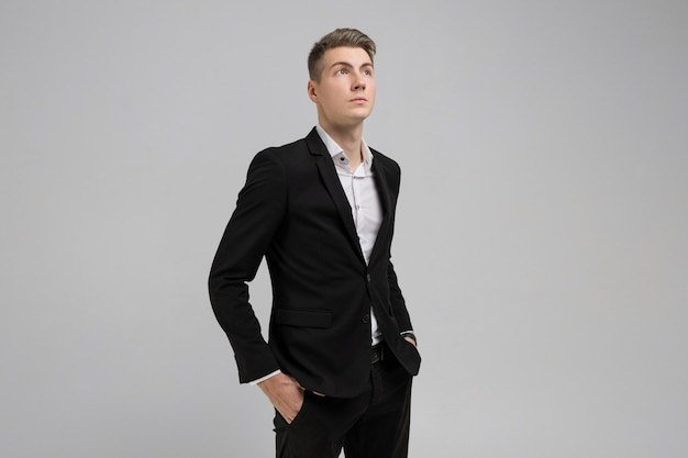 Portrait of young man with hands in pockets in black suit isolated on white background