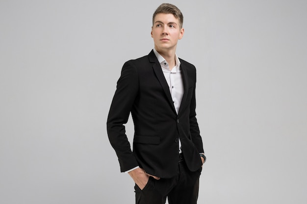 Portrait of young man with hands in pockets in black suit isolated on white tshirt