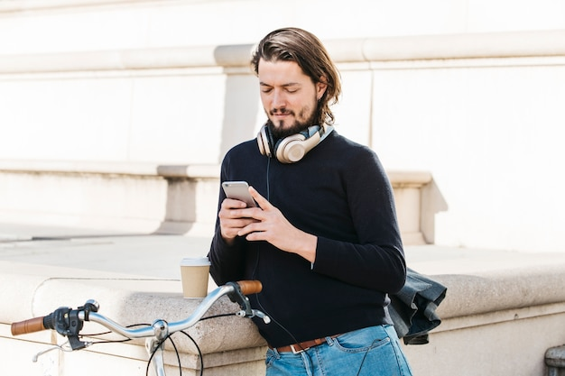 Portrait of a young man with headphone around his neck using mobile phone at outdoors