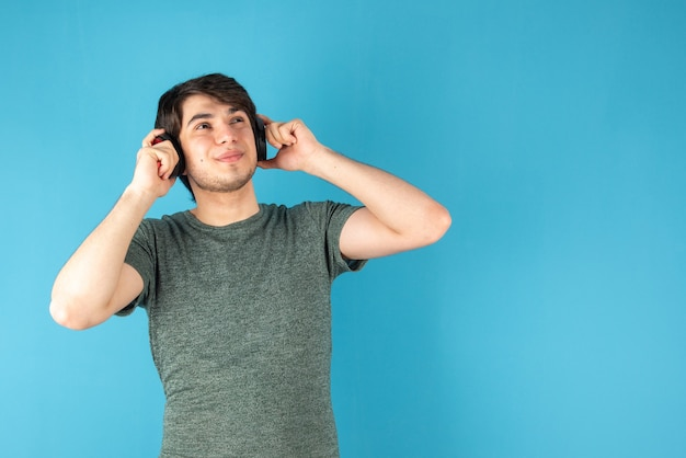 Portrait of young man with headphones on head against blue .