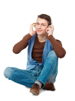 Portrait of young man with headphones sitting on the floor isolated on white background