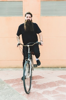 Portrait of a young man with long beard riding the bicycle