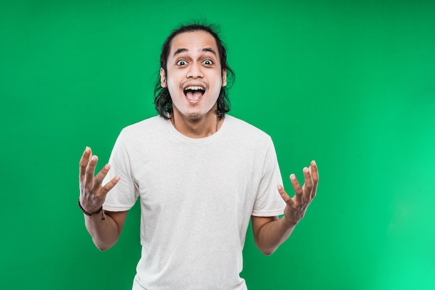 Portrait of a young man with long black hair with a shocked expression on a green wall