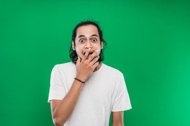 Portrait of a young man with long black hair with a shocked facial expression on a green background