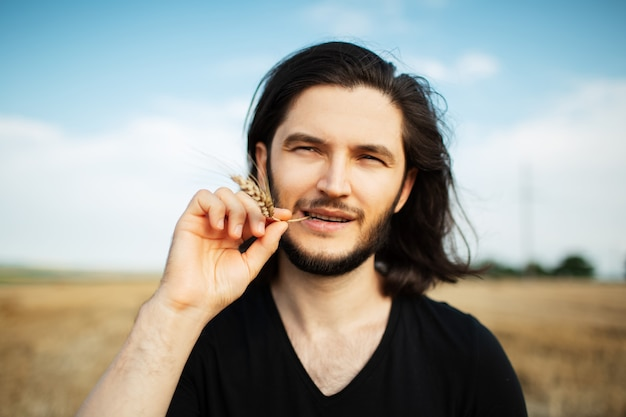 Portrait of young man with long hair holding wheat spike in mouth.