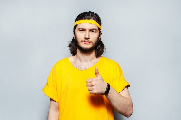 Portrait of young man with long hair wearing yellow shirt, showing thumb up on