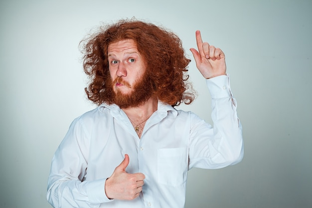 Portrait of young man with long red hair and with shocked facial expression on gray background showing up