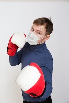 Портрет молодого человека с медицинской маской на лице в боксерских перчатках крупным планом на белом фоне