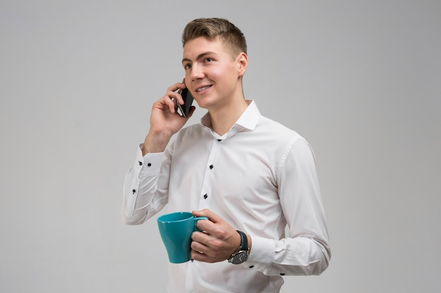Portrait of young man with mug and mobile phone in his hands on white