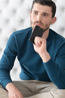 Portrait of a young man with phone at home