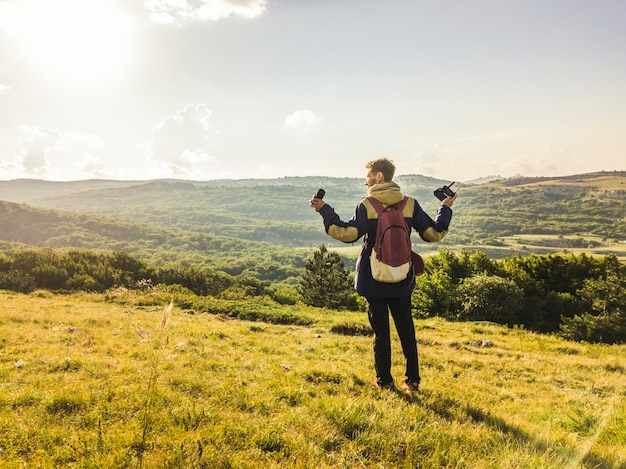 Portrait of young man with photography equipment and raised hands walking on the mountain field