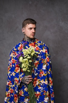 Portrait of young man with pierced ears and nose holding purple and yellow limonium flowers in hand